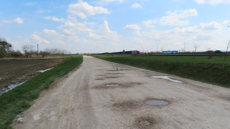 Wyboista, rzadko uczęszczana,  droga wzdłuż autostrady